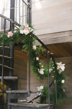 Soft green garland wrapped around the banister for this farm wedding was made even more romantic with the addition of soft greens and pinks