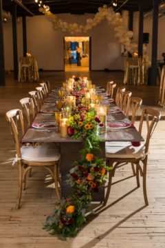 Chic long table we designed for The Knot Market Mixer complete with greenery runner details and gold candle holders