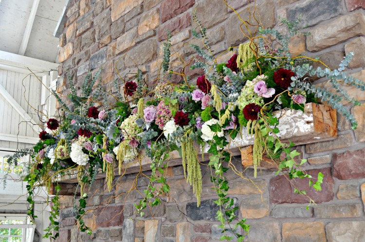 We mixed different pieces of greenery and pops of purple, white, red and blue for this elegant mantle design for our bride and groom.
