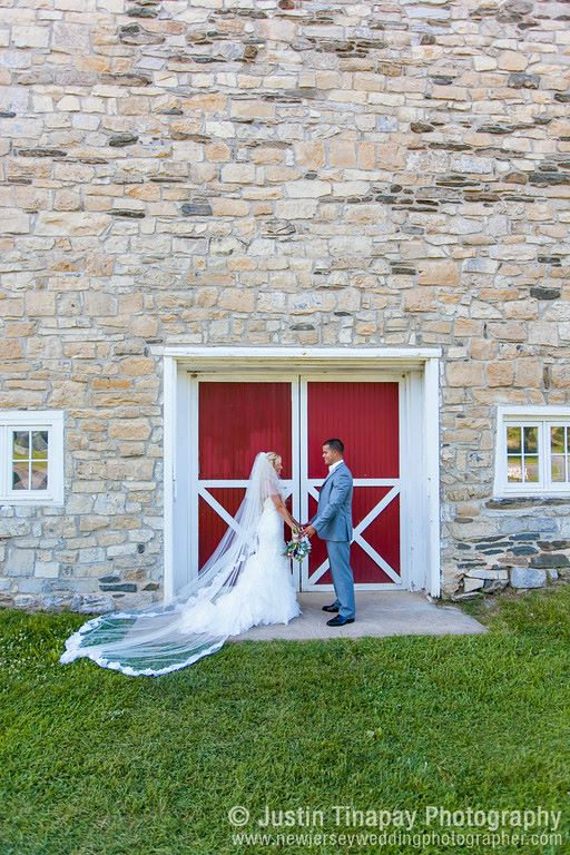 The perfect lace mermaid gown for a country farm wedding. We love how our bride paired it with a romantic super long veil!
