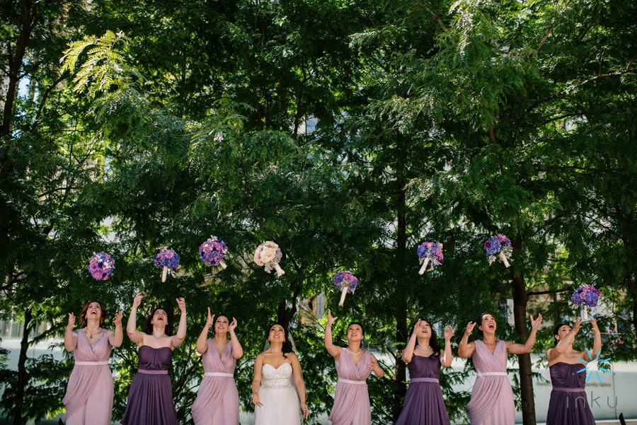 bride and bridesmaids tossing purple bouquets