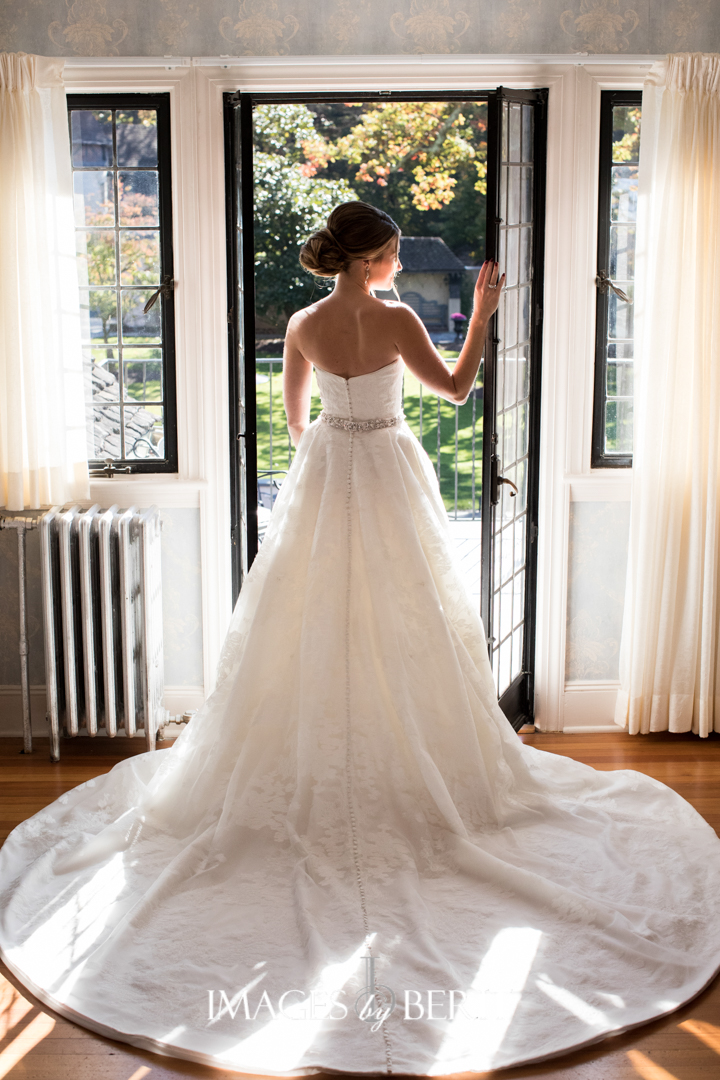 back of bride in dress standing in window