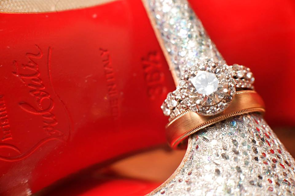diamond engagement ring and gold wedding band on heel of shoe