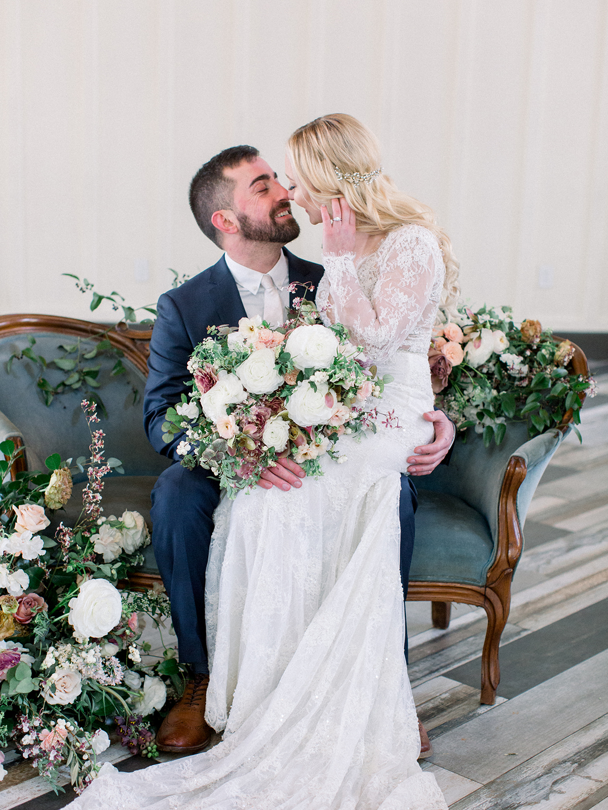 bride sitting on groom's lap on vintage blue couch covered in flowers