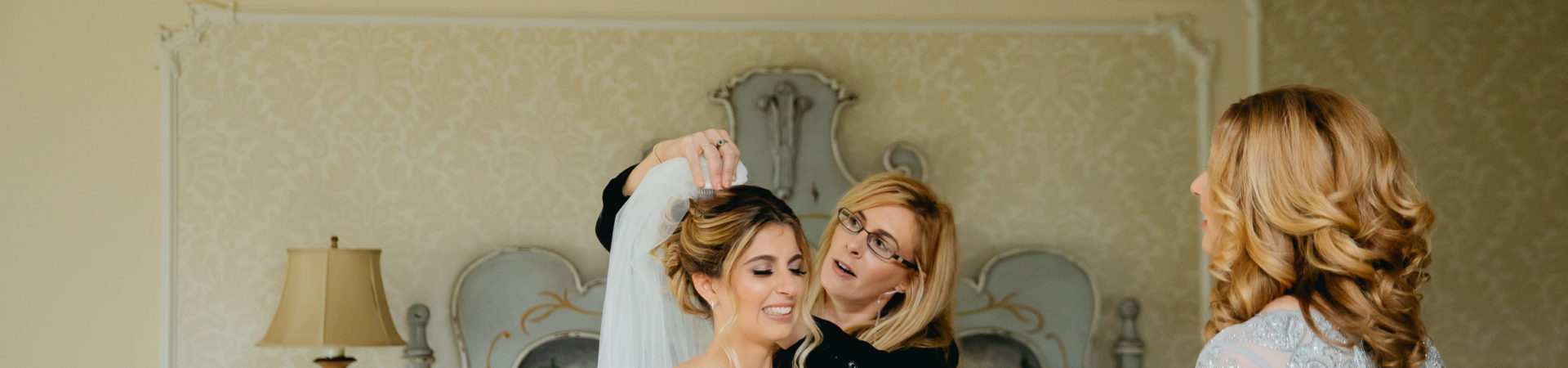 wedding planner placing veil on bride's head