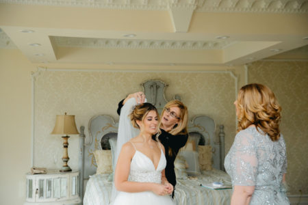 wedding planner placing veil on bride's head