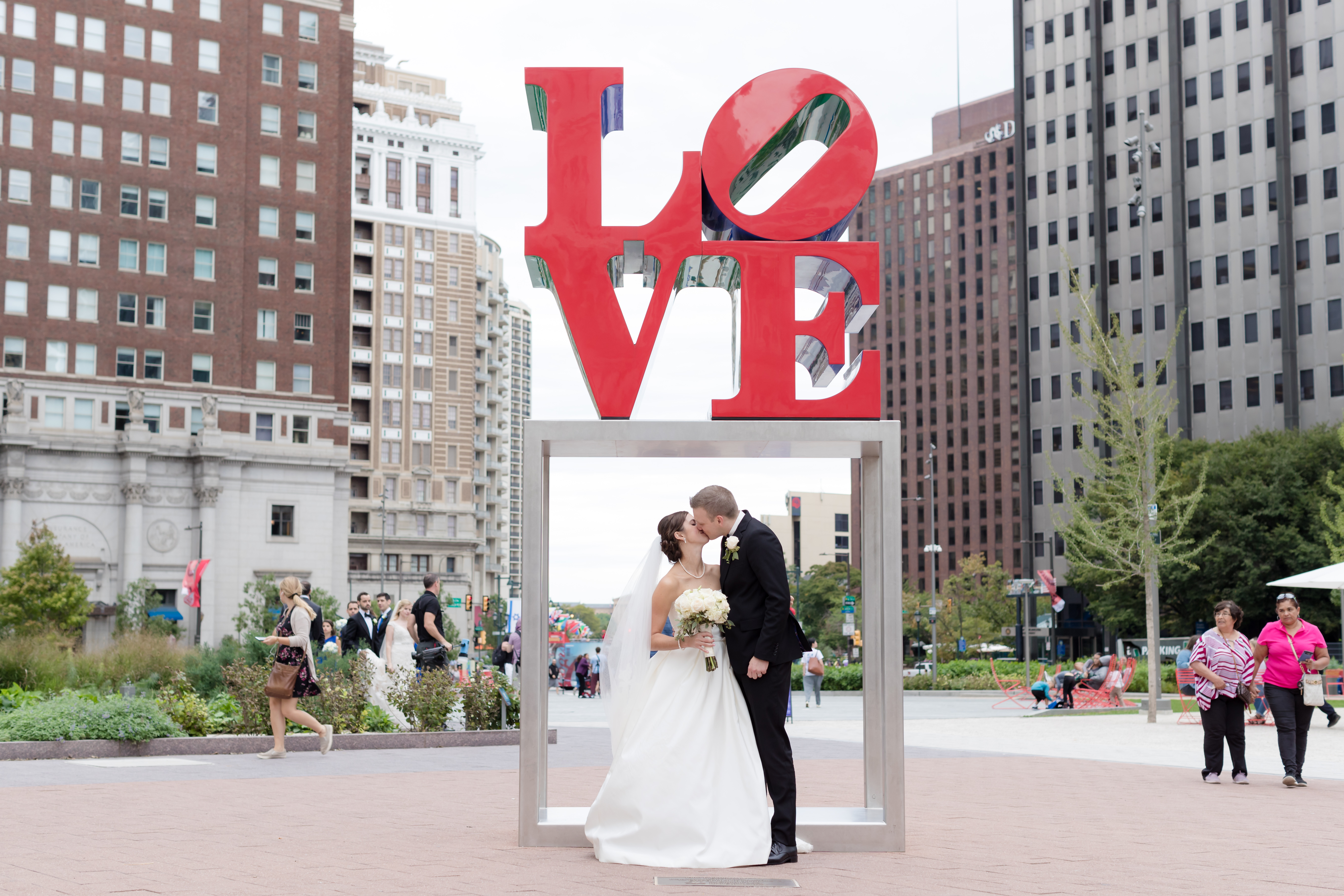 bride and groom outside love statue in philadelphia