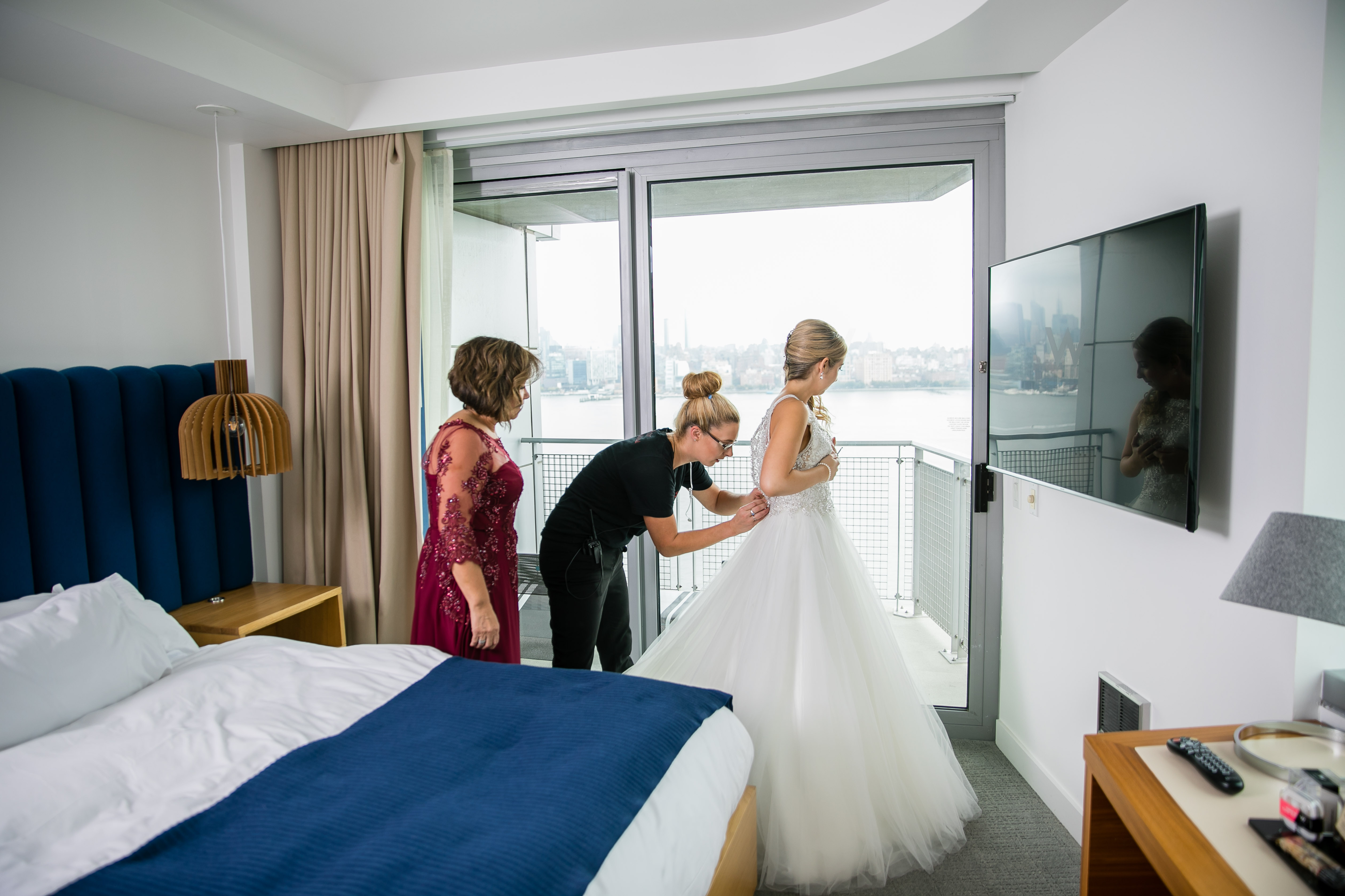 wedding planner zipping up bride's dress with mother of the bride