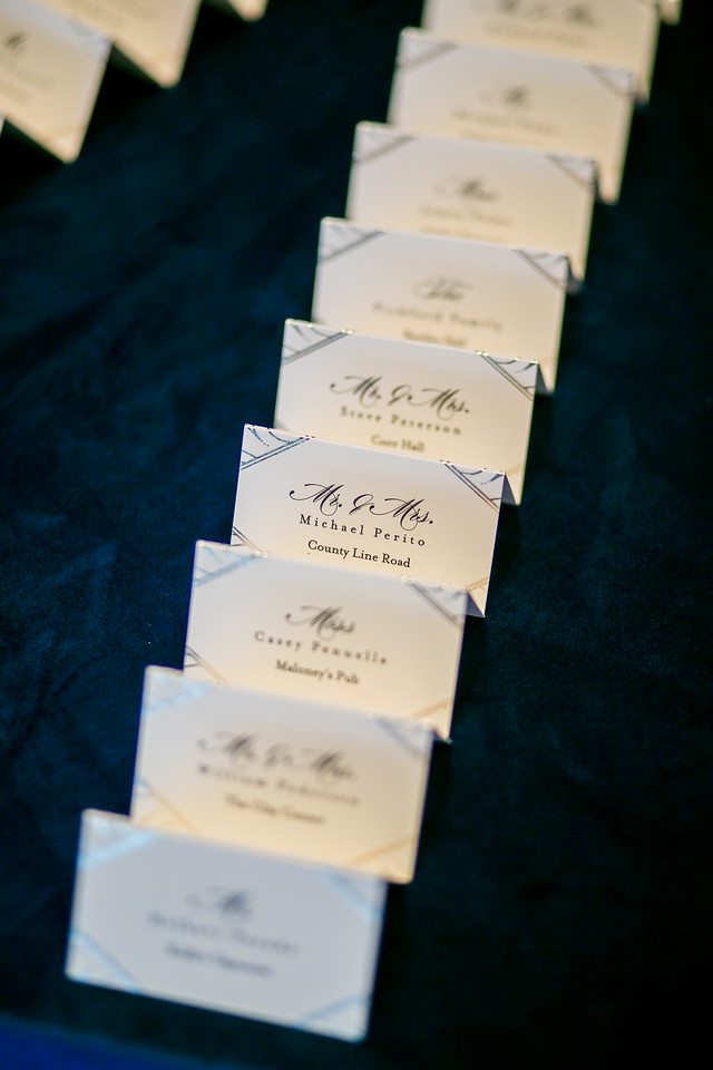 gold foil escort cards on blue linen