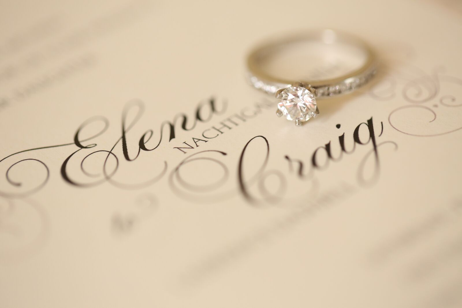 cream colored invitation with diamond solitaire engagement ring
