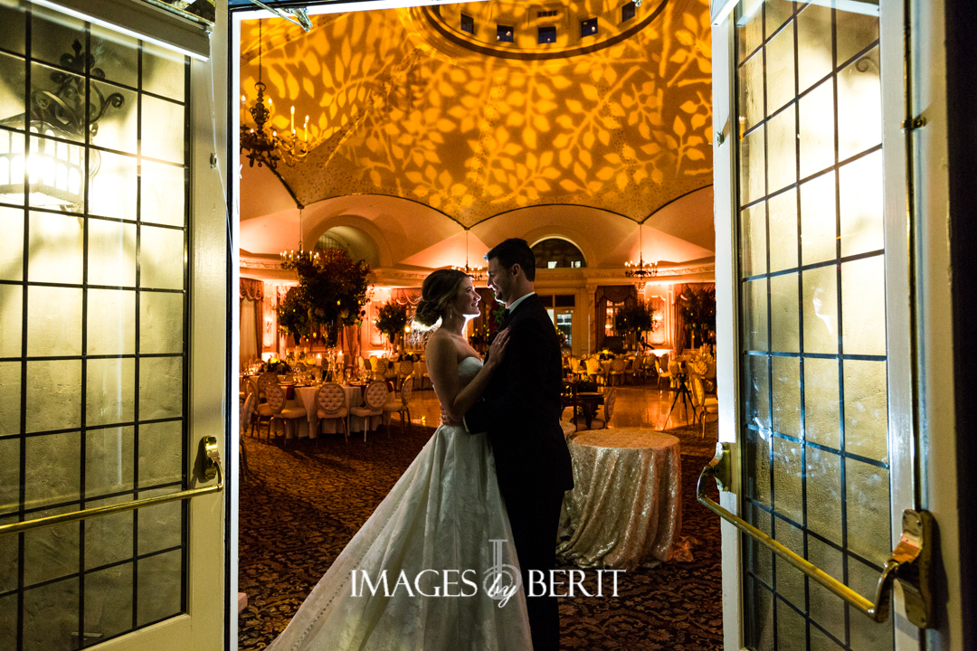 bride and groom standing in golden ballroom