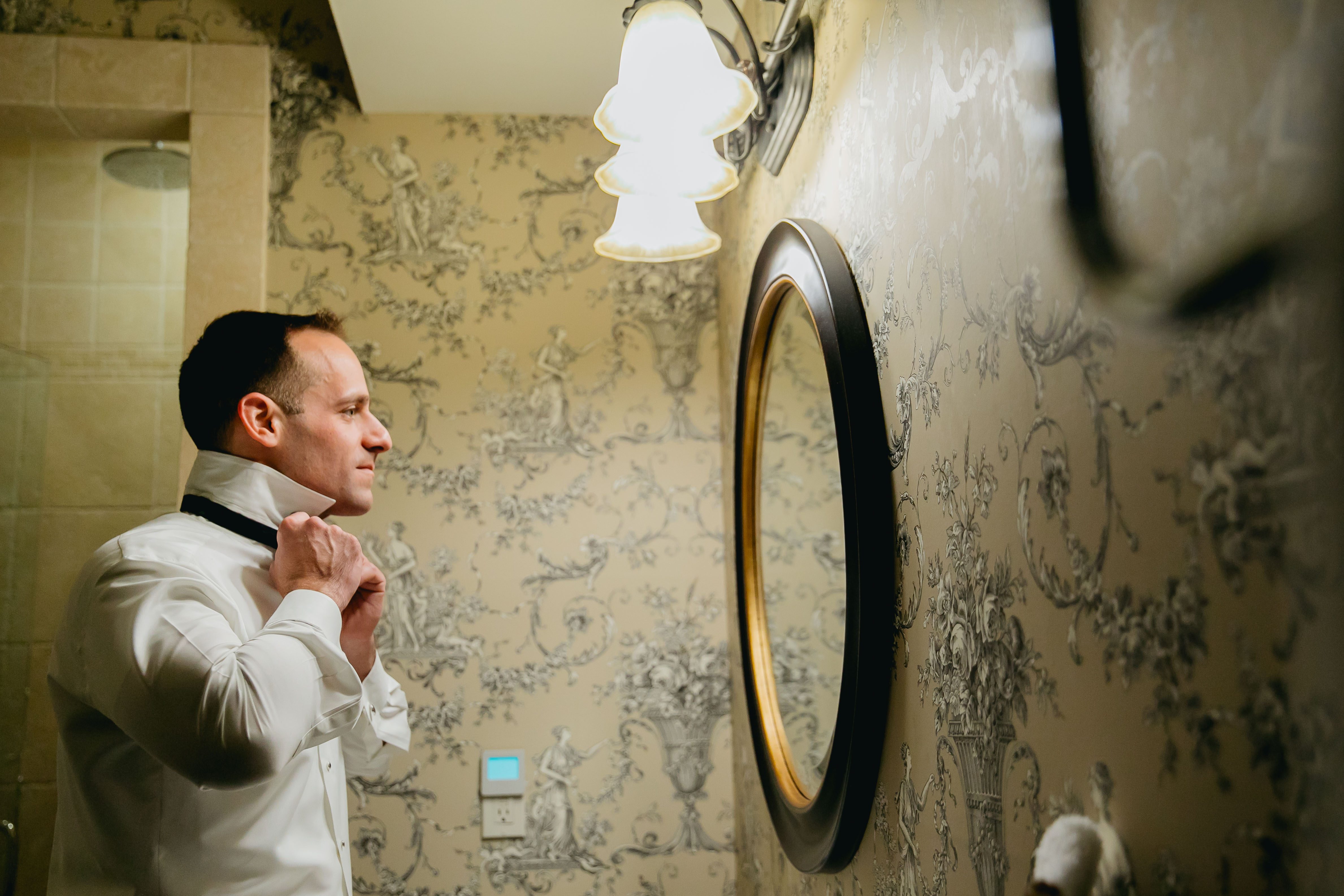 groom adjusting bow tie in mirror