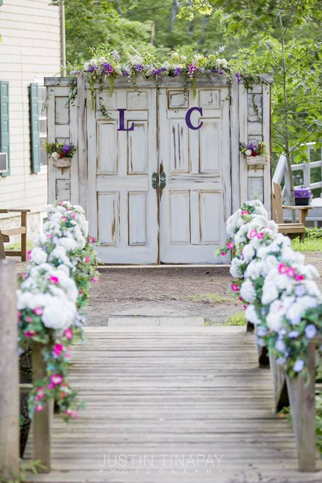 flowers on bridge leading to rustic door