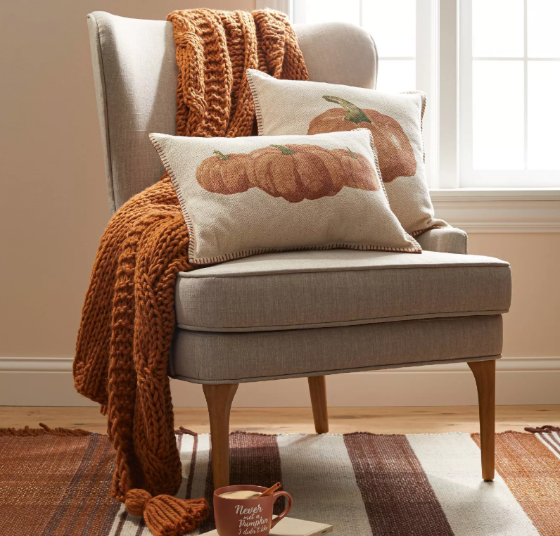 chair with orange blanket and pumpkin pillows