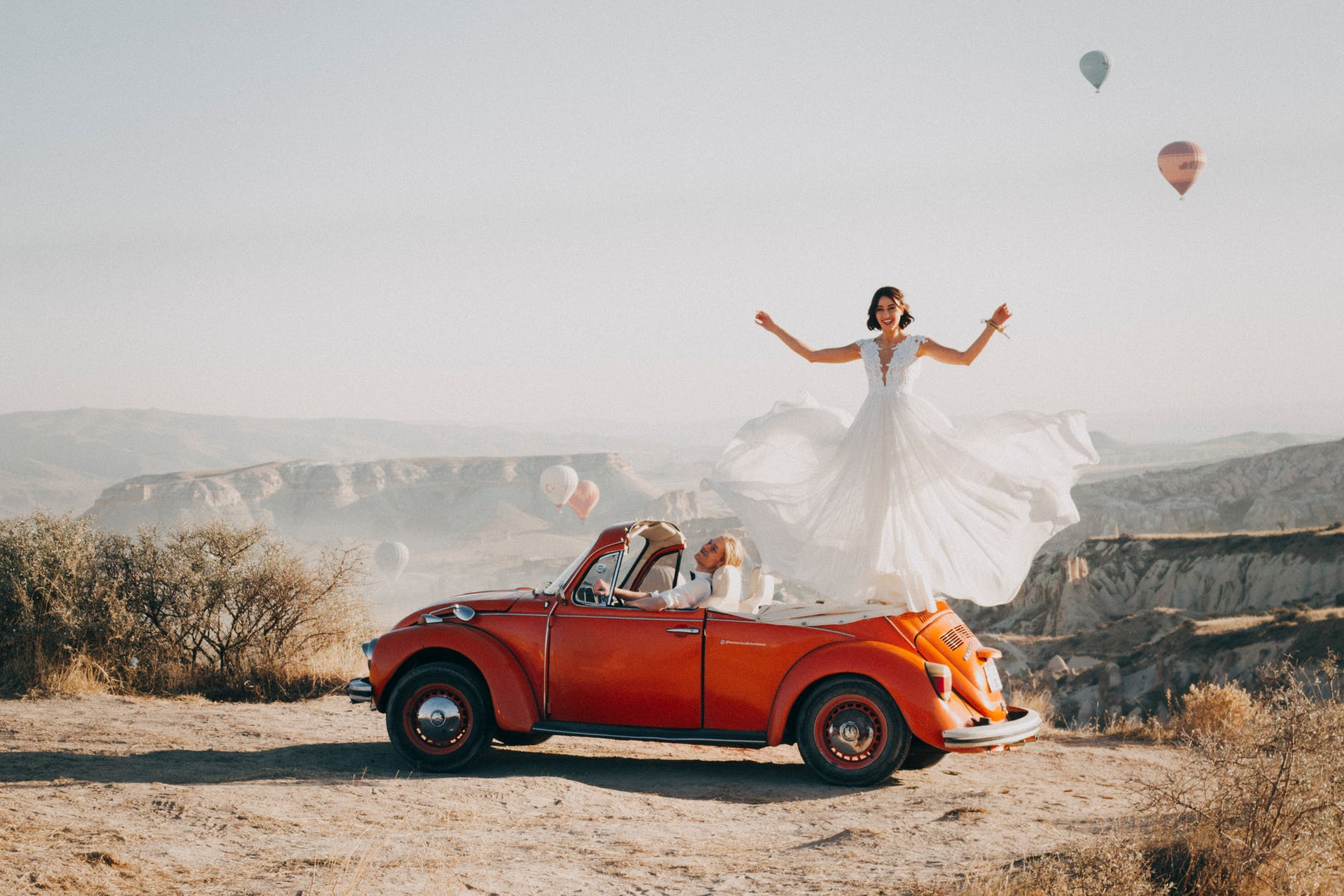 bride standing on car