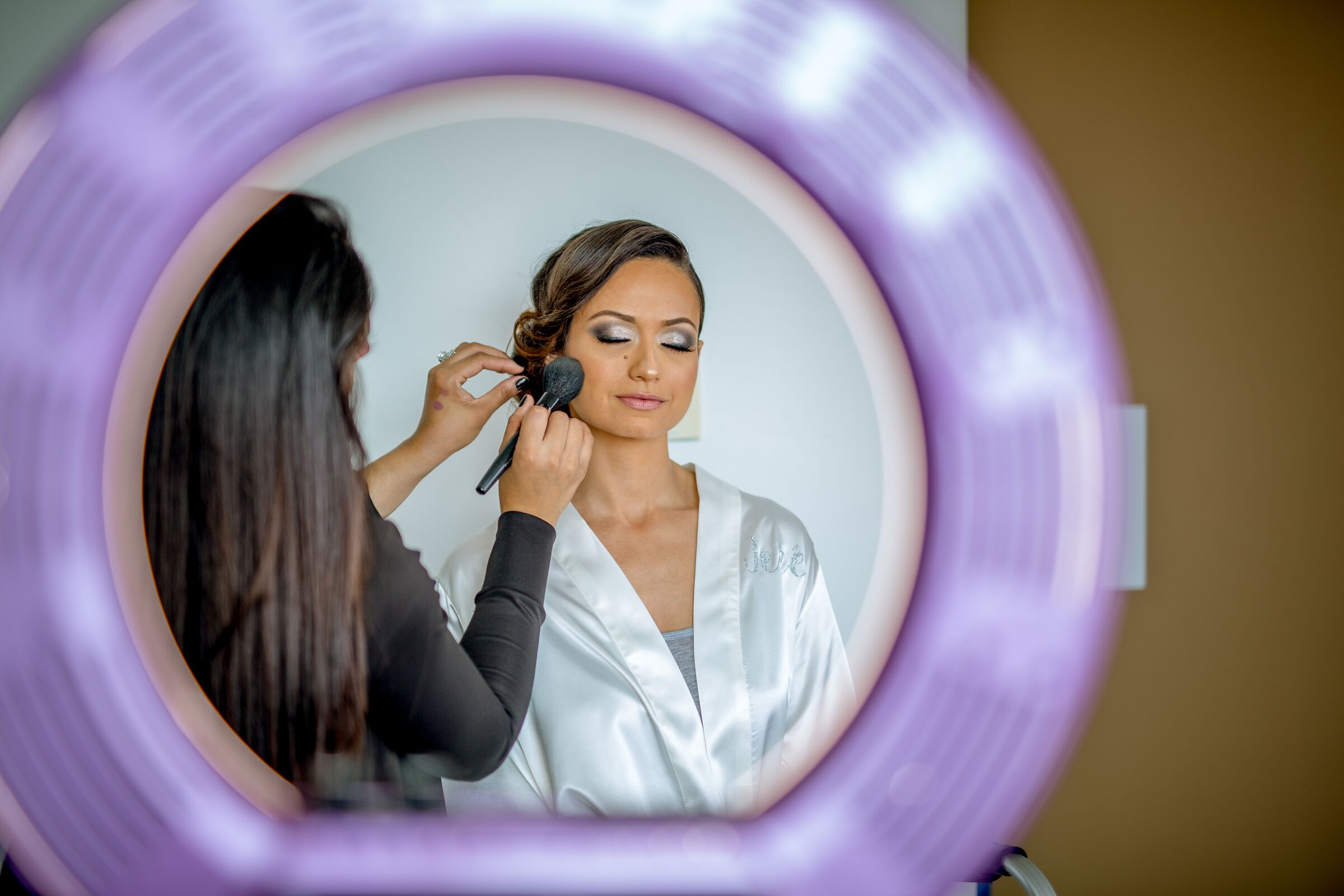 bride getting make up done in mirror