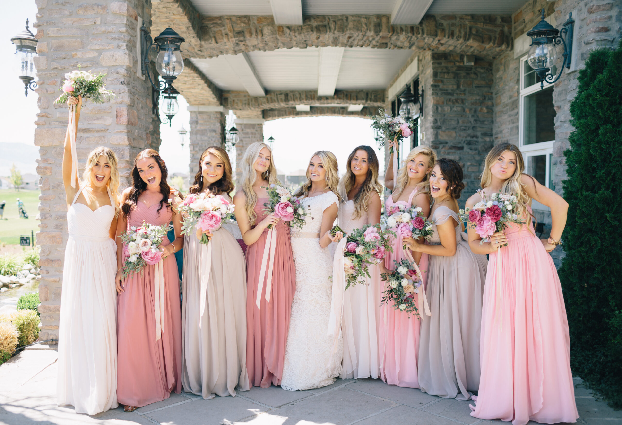 bridesmaids in shades of pink outside with the bride in the middle