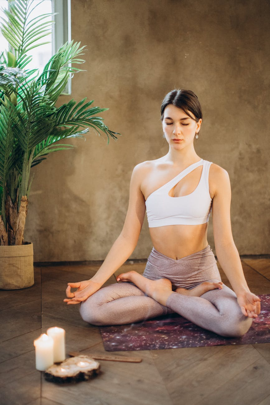 woman meditating near plant